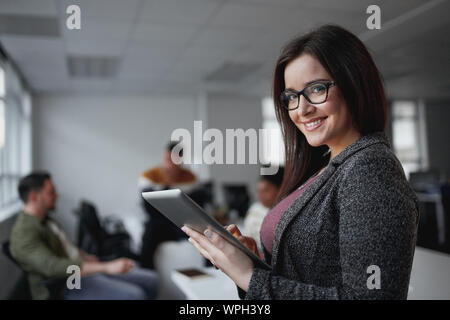 Portrait of happy businesswoman holding digital tablet in office standing in front of colleagues discussing au contexte
