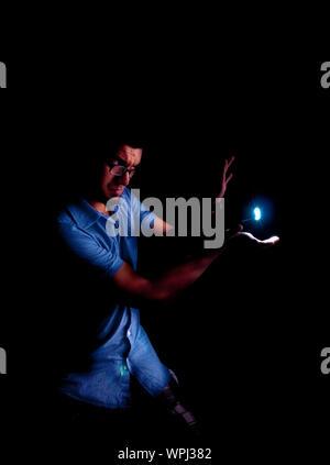 Magicien montrant tour de magie en étant debout sur fond noir