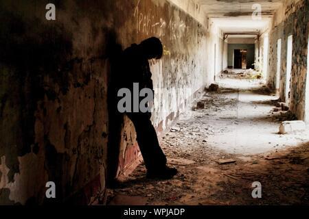 Silhouette de l'homme appuyé contre le mur du couloir Banque D'Images