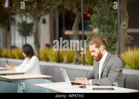 Jeune homme d'affaires graves en fonction de se concentrer sur son travail en ligne il la saisie sur ordinateur portable avec businesswoman en arrière-plan de cafe