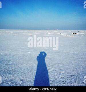 Ombre de l'homme sur le terrain couvert de neige contre Ciel Bleu clair Banque D'Images