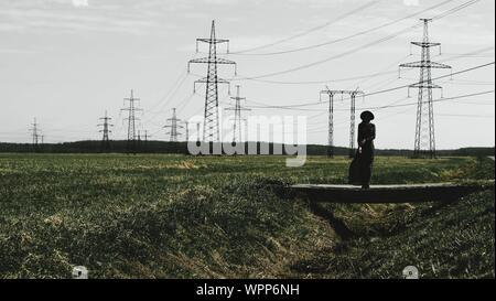 Femme Debout sur le terrain contre Sky Banque D'Images