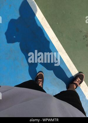 La section basse Vue de l'homme debout sur un court de tennis Banque D'Images