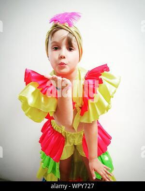 Portrait of Teenage Girl in Costume Rumba Blowing Kiss Against White Background Banque D'Images