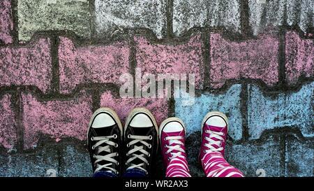 Directement au-dessus de la Femme et fille avec des chaussures de toile debout sur un passage Pavé Banque D'Images