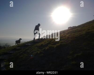 Silhouette Of Man with Dog Walking On suit sur Hill Banque D'Images