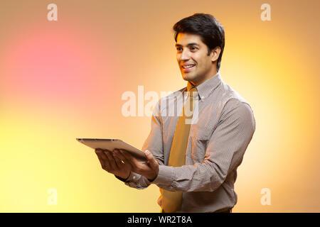 Homme d'affaires tenant une tablette numérique et souriant Banque D'Images