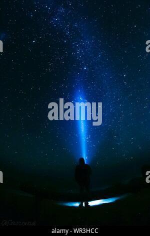 Vue arrière de l'homme avec une lampe de poche à la recherche de ciel étoilé Banque D'Images