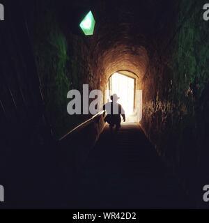 Vue arrière de l'homme Silhouette en descente comme suit dans le tunnel Banque D'Images