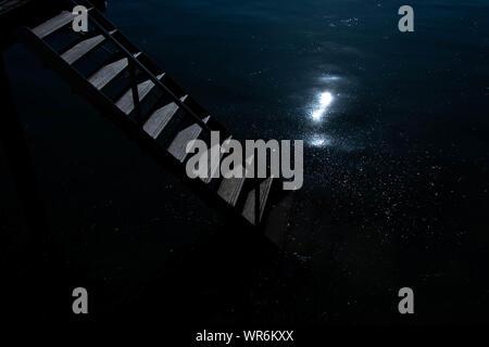 Un escalier descendant dans l'eau de nuit comme le clair de lune se reflète sur la surface des eaux Banque D'Images