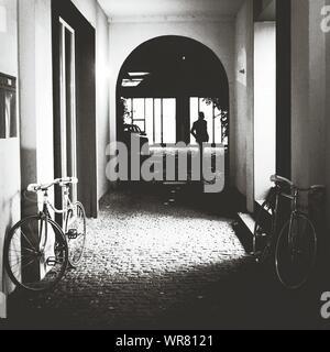 S'appuyant sur des vélos contre un mur d'ossature Man Standing In House Banque D'Images