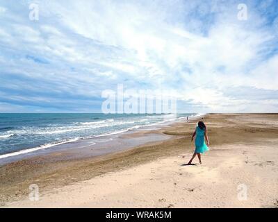 Toute la longueur de femme en robe bleue à la marche ciel nuageux sur Sunny Day Banque D'Images