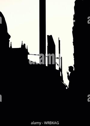 Silhouette Man Leaning On Wall Against Clear Sky Banque D'Images