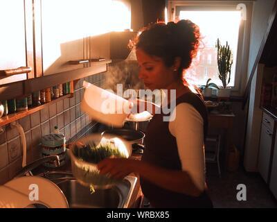 Jeune femme enceinte laver les légumes dans la cuisine Banque D'Images