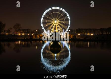 PARIS, FRANCE - Le 3 décembre 2013: lluminated Grande Roue la nuit sur la Place de la Concorde, en réfléchissant à un bassin dans le jardin des Tuileries. Banque D'Images