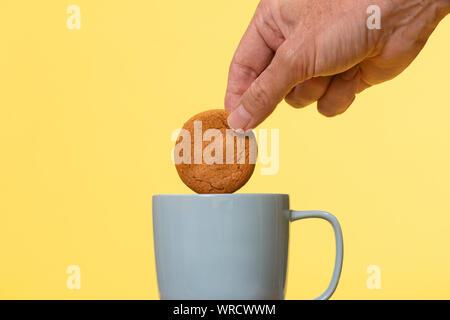 Tremper un biscuit dans une tasse de thé. Banque D'Images