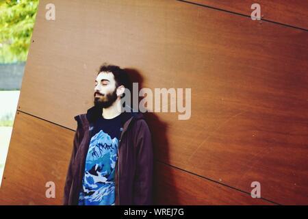 Jeune homme à l'écart debout contre le mur Banque D'Images