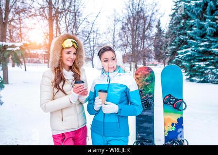 Deux copines sont heureux de sourire, en hiver à ski resort, holding hot cup avec des boissons, des amoncellements de neige de fond, surf des neiges. Camping Banque D'Images
