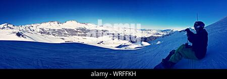 Vue panoramique de l'homme assis sur la neige contre le ciel Banque D'Images