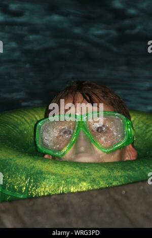 Close-up Portrait of Teenage Boy portant des lunettes de natation en piscine Banque D'Images