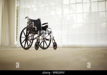 Assis en fauteuil roulant dans une chambre vide. Banque D'Images