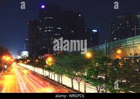 Sentiers de feux de circulation sur route avec des gratte-ciel en arrière-plan Banque D'Images