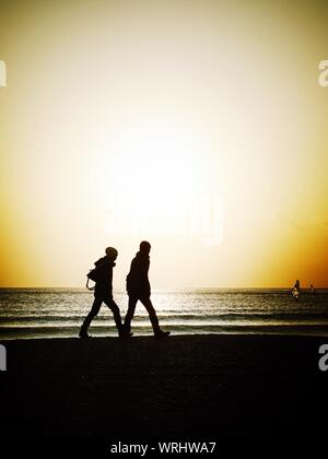 Silhouette of People Walking On Beach at Sunset Banque D'Images