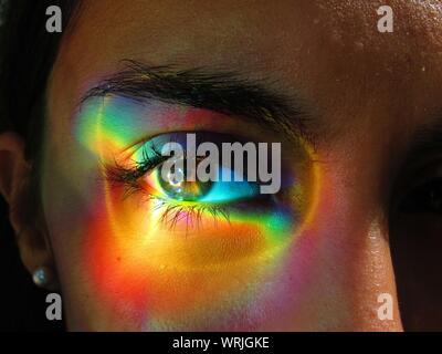 Close-up Portrait of Woman Eye sur lumière multicolore Banque D'Images