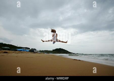 Low Angle View of woman doing The Splits sur Beach Against Cloudy Sky Banque D'Images