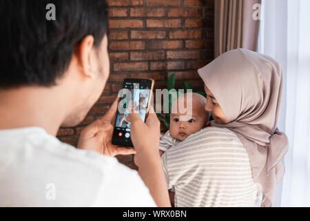 Père de prendre photo de son bébé bébé à la maison tout en étant porté par mère Banque D'Images