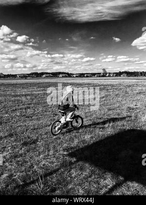 Boy Riding Bicycle On Grassy Field Against Cloudy Sky sur Sunny Day Banque D'Images