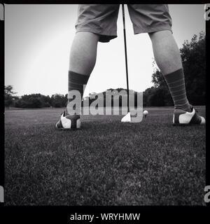 La section basse de golfeur en jouant au golf sur terrain