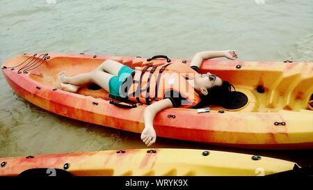 High Angle View of Happy Woman Lying On kayak en rivière