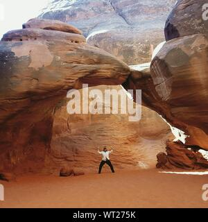 Woman Standing Under Rock Formations in Desert Banque D'Images