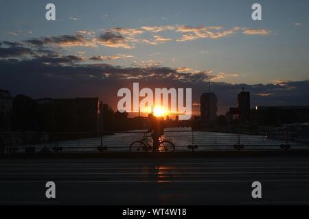Vélo homme sur pont sur la rivière contre ciel nuageux pendant le coucher du soleil Banque D'Images