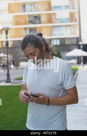 Middle aged man standing on the street, contrôler son smartphone Banque D'Images