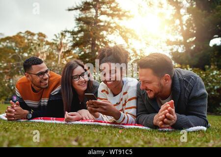 Smiling african american woman multiethnique avec son groupe d'amis de SMS sur téléphone mobile dans un parc - très heureux groupe d'amis Banque D'Images