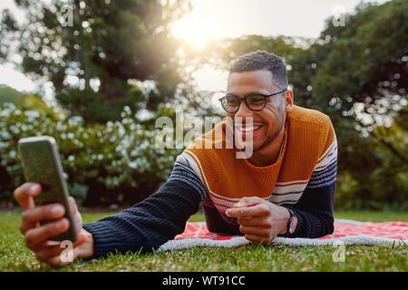 Portrait of a smiling young african american man lying on blanket sur l'herbe verte dans le parc en tenant sur selfies téléphone mobile au collégial - universitaire