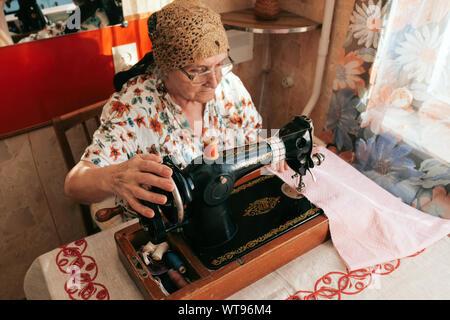 Portrait de 70 ans senior woman in spectacles à l'aide de la machine à coudre, travailler de la maison. Travailler pour les personnes âgées, les vêtements et d'adaptation de concept. Banque D'Images