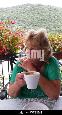 Senior Woman Looking Away alors que Holding Coffee Cup sur balcon Banque D'Images
