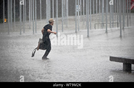Homme qui court dans la pluie sur rue au centre-ville Banque D'Images