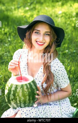 Smiling girl in black la chaleur est holding watermelon avec paille cocktail sur la nature de fond vert. Jeune femme avec la pastèque. Banque D'Images