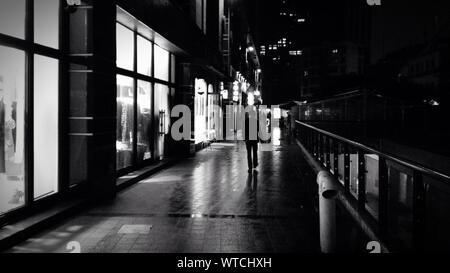 Vue arrière sur toute la longueur de l'homme marchant sur la rue humide par des bâtiments dans la nuit Banque D'Images