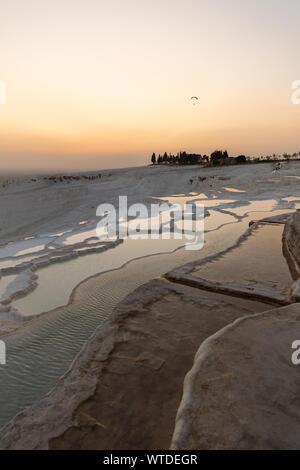 Coucher de soleil sur des travertins de Pamukkale - Château de coton - Coton Palace Turquie avec de belles couleurs et de réflexions sur l'eau des piscines Banque D'Images