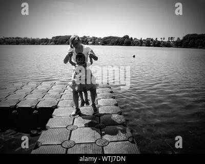 Jouer avec mère fille sur la jetée au lac Banque D'Images