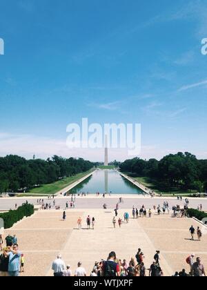 Les gens qui suivent le Washington Monument contre le ciel bleu