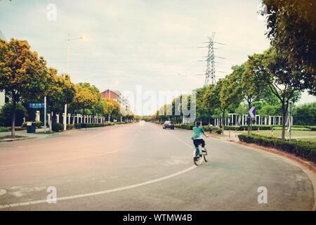 Vue arrière du Woman Riding Bicycle On Road Against Sky Banque D'Images