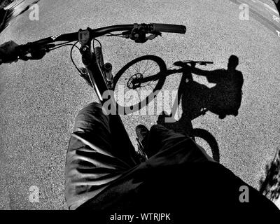 Ombre de Man Riding Bicycle On Street Banque D'Images