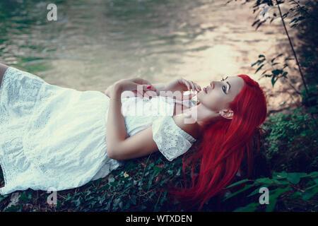 Belle jeune fille se reposant dans l'eau. Jeune femme à la robe blanche est assis sur la pierre au milieu d'un ruisseau. Banque D'Images