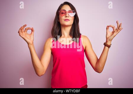 Belle femme portant des lunettes de soleil en forme de coeur rose drôle sur fond rose isolé vous détendre et souriant avec les yeux fermé faisant geste de méditation w Banque D'Images